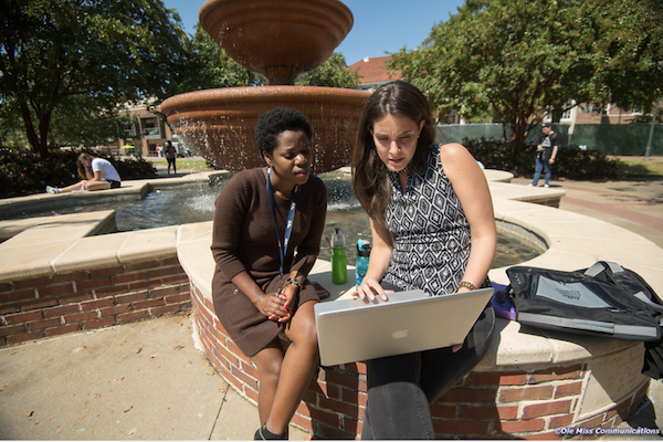 Neema Loy, left, a Ph.D. student in linguistics from Tanzania, and Marcella Cascione Netto, a masters student in linguistics from Brazil, confer with each other at the fountain in the quad. Photo by Kevin Bain/ UM Communications
